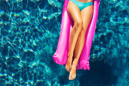 Beautiful sexy young woman relaxing floating on raft in luxury swimming pool