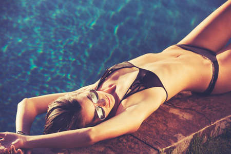 fashion: Fashion lifestyle, beautiful woman in swimwear relaxing by the pool at sunset