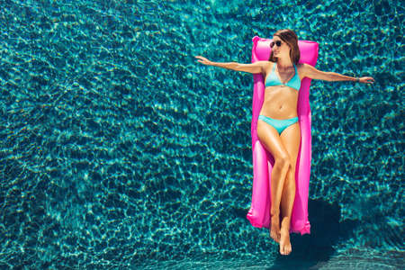 float: Beautiful young woman relaxing floating on raft in luxury swimming pool Stock Photo
