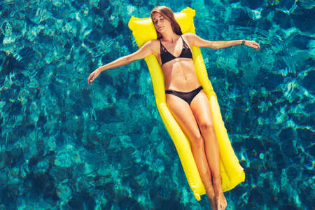 raft: Beautiful woman relaxing floating on raft in luxury swimming pool Stock Photo