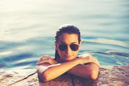 サンセット、豪華なリゾート ファッション ライフ スタイル プールでリラックスした美しい若い女性