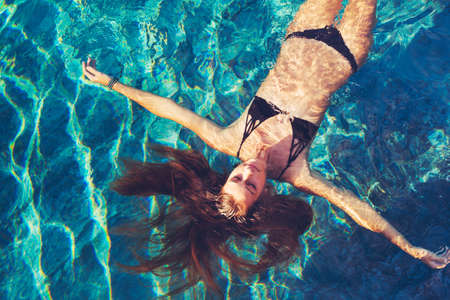 Beautiful young woman floating in pool relaxing