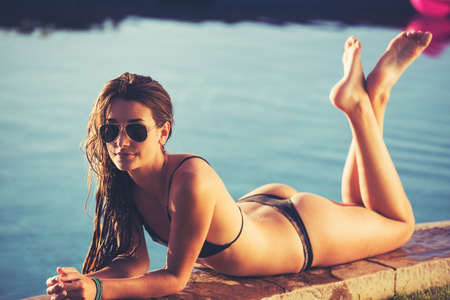Fashion lifestyle, beautiful woman in swimwear relaxing by the pool at sunset
