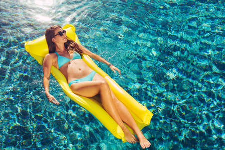 Beautiful sexy young woman in bikini relaxing floating on raft in luxury swimming pool Stock fotó - 52376361