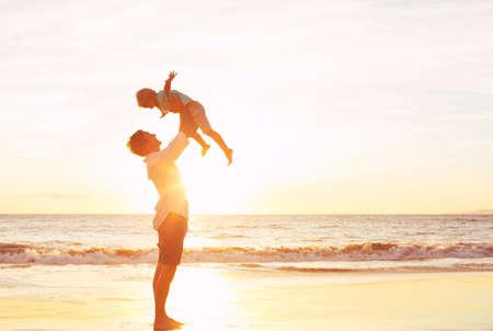 Vader en zoon spelen op het strand bij zonsondergang