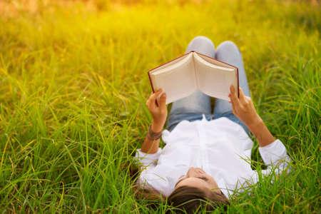 Giovane donna che gode di un libro di lettura esterna Archivio Fotografico