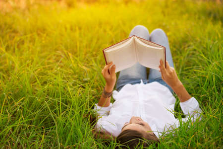 Young Woman Enjoying a Book Reading Outdoors Imagens
