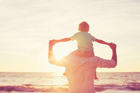 Отец и сын играет на пляже на закате, имея высокое качество семьи время вместе.