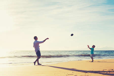family activities: Father and Son Playing Catch Throwing Football on the Beach at Sunset Stock Photo