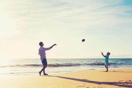 Vater und Sohn spielen Fangen Werfen Fußball am Strand bei Sonnenuntergang