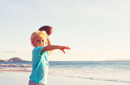 coger: El muchacho joven que juega el retén Lanzamiento de fútbol en la playa Foto de archivo