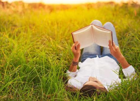 personas leyendo: Mujer joven que goza de un libro de lectura al aire libre Foto de archivo