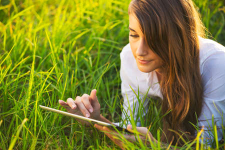 mobile technology: Happy Young Woman Using Tablet Outdoors, Mobile Technology Concept Stock Photo