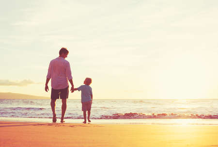 Father and Son Holding Hands Walking Together on the Beach at Sunset Reklamní fotografie - 48345094