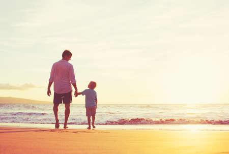 Vader en zoon hand in hand lopen samen op het strand bij zonsondergang Stockfoto - 48345094