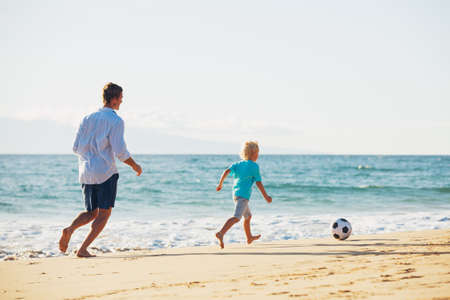 playful: Happy Father and Son Having Fun Playing Soccer on the Beach Stock Photo