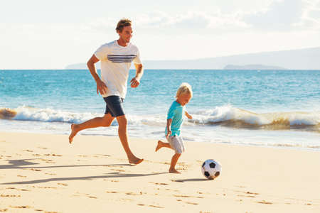 an adult person: Happy Father and Son Having Fun Playing Soccer on the Beach Stock Photo