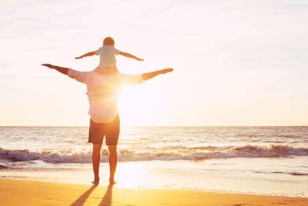 padres: Padre e hijo que juegan en la playa en la puesta del sol, Vista Calidad familia tiempo juntos. Foto de archivo