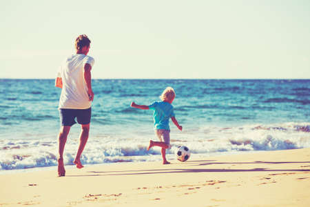 football play: Happy Father and Son Having Fun Playing Soccer on the Beach Stock Photo