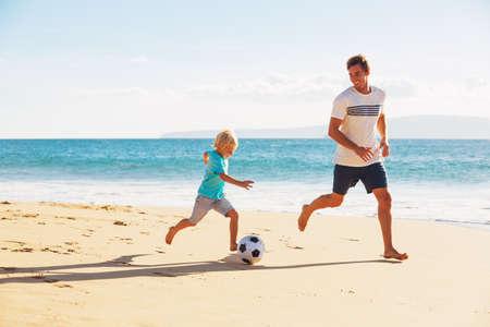 Feliz pai e filho se divertindo jogando futebol na praia