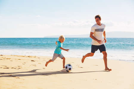 Happy Father and Son Having Fun Playing Soccer on the Beach Stockfoto