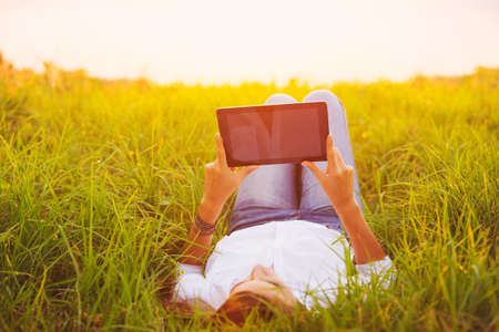 Happy Young Woman Using Tablet Outdoors