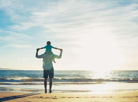 Vader en zoon spelen op het strand bij zonsondergang, hebben kwaliteit familie tijd samen.
