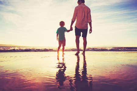 父と息子は、夕暮れのビーチで一緒に歩いて手を繋いでいます。