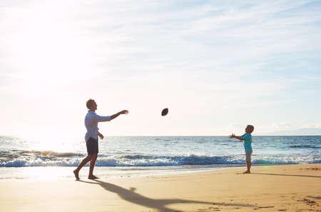 coger: Padre e hijo que juega el retén Lanzamiento de fútbol en la playa en la puesta del sol
