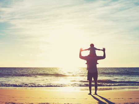 父と息子は、夕暮れのビーチで遊んで