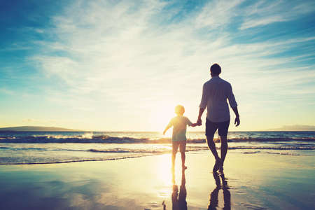해질녘 해변에서 함께 걷고 아버지와 아들 손을 잡고