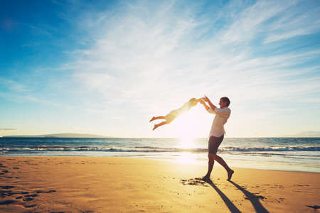 Отец и сын играет на пляже на закате