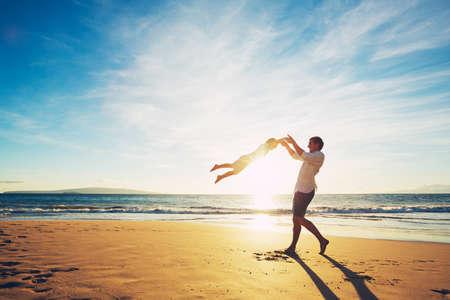 Padre e figlio che giocano sulla spiaggia al tramonto Archivio Fotografico