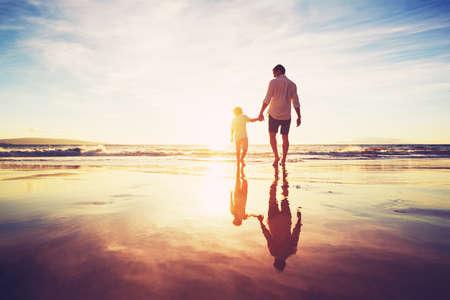 Vader en zoon hand in hand lopen samen op het strand bij zonsondergang