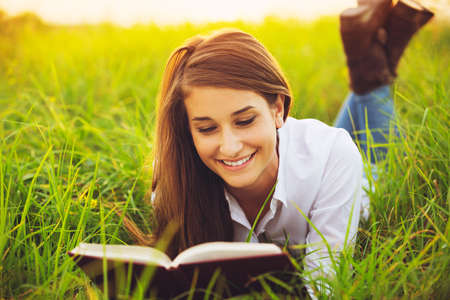 Young Woman Enjoying a Book Reading Outdoors Banco de Imagens