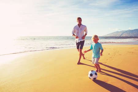 soccer: Happy Father and Son Having Fun Playing Soccer on the Beach at Sunset