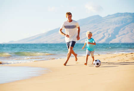 kids fun: Happy Father and Son Having Fun Playing Soccer on the Beach Stock Photo