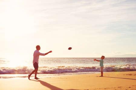 父と息子の演奏を夕暮れビーチでサッカーを投げキャッチします。 写真素材