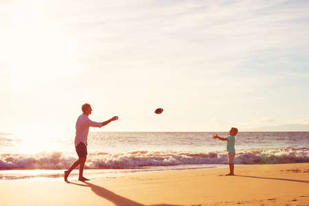 Father and Son Playing Catch Throwing Football on the Beach at Sunset Stock Photo
