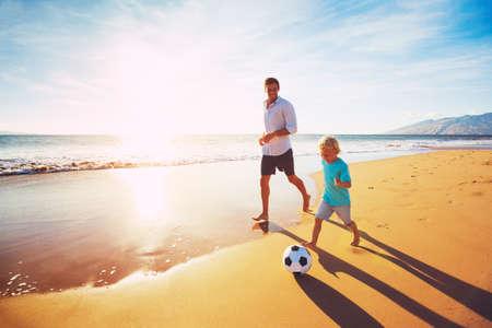 Счастливый отец и сын весело играя футбол на пляже на закате