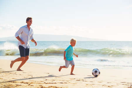 Happy Father and Son Having Fun Playing Soccer on the Beach Zdjęcie Seryjne
