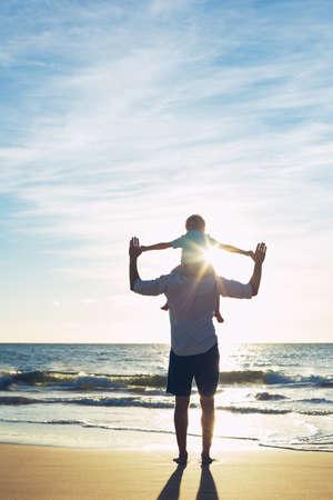 Pai e filho que jogam na praia no por do sol