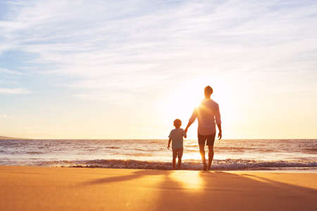 Father and Son Holding Hands Walking Together on the Beach at Sunset Stock Photo - 48345341