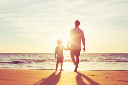 kids holding hands: Father and Son Holding Hands Walking Together on the Beach at Sunset