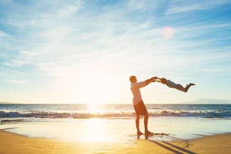 convivencia familiar: Padre feliz alegre e hijo que juegan en la playa en la puesta del sol. Paternidad Familia Concepto