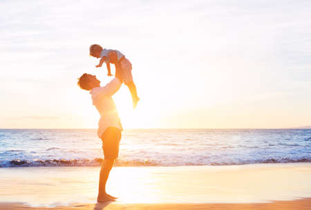 Счастливый Радостный отец и сын, весело играя на пляже на закате. Отцовство концепция семьи