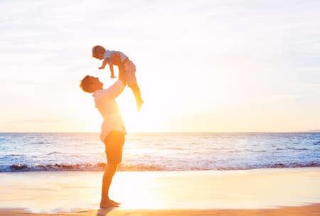 Pai feliz alegre e filho que têm o divertimento jogar na praia no por do sol. Paternidade conceito de família