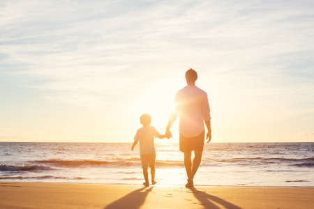 day dream: Father and Son Walking Together on the Beach at Sunset. Fatherhood Family Concept