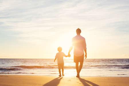dia soleado: Padre e hijo caminando juntos en la playa al atardecer. Concepto de familia paternidad