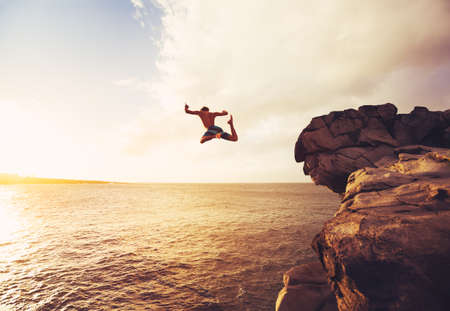 brincando: Acantilado de salto en el océano en la puesta del sol, aventura al aire libre Estilo de vida